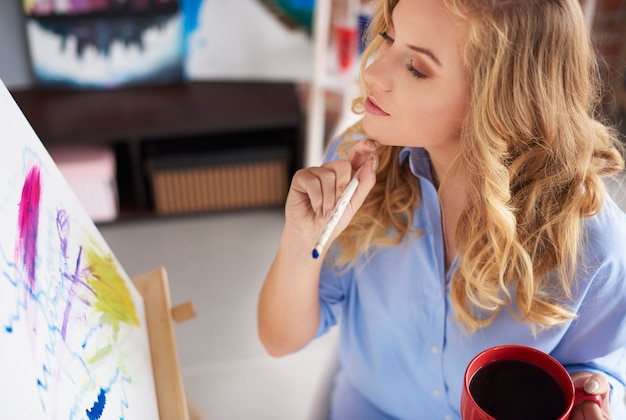 Vrouw kijkt naar haar geschilderde afbeelding