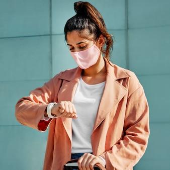 Vrouw kijkt naar haar horloge terwijl ze een medisch masker draagt tijdens een pandemie op de luchthaven