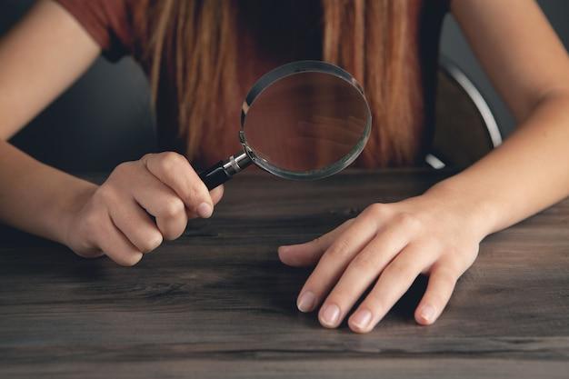 Vrouw kijkt naar haar nagels met een vergrootglas