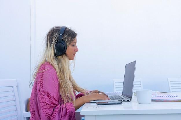 Vrouw kijkt naar laptop telewerken zijaanzicht