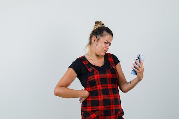 Vrouw kijkt naar mobiele telefoon in schort jurk en kijkt aarzelend, vooraanzicht.