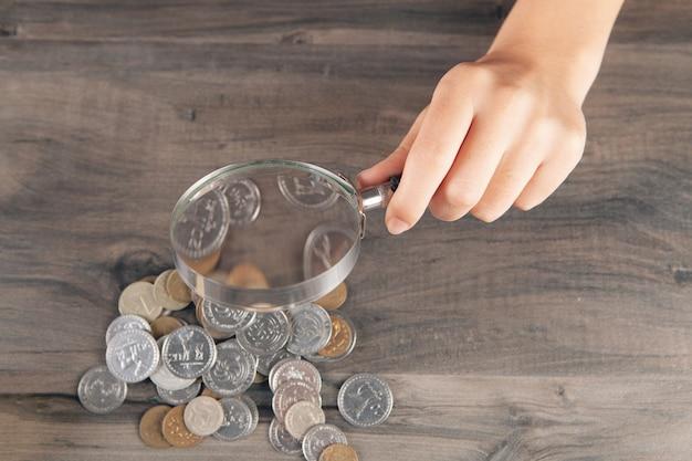 Vrouw kijkt naar munten met een vergrootglas