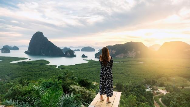 Vrouw kijkt naar phang nga bay in zonsopgang vanaf samed nang chee viewpoint, thailand