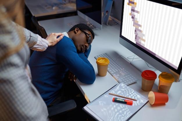 Vrouw kijkt naar slapende manager, nachtelijke kantoorlevensstijl. vermoeide mannelijke personen op laptop, moderne werkplek