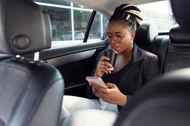 Vrouw kijkt naar smartphone en heeft koffie in haar auto
