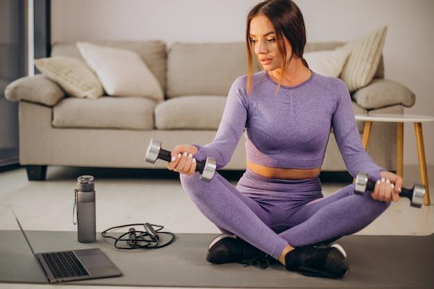 Vrouw kijkt naar tutorials en traint vanuit huis op mat met springtouw en dumbbells