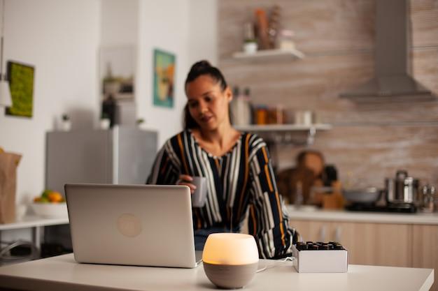 Vrouw kijkt naar video op laptop en ontspant met etherische oliën aromatherapie van oliediffuser