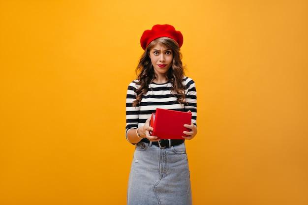 Vrouw kijkt ontevreden na het openen van de rode doos. triest meisje met krullend haar in rode baret en denim rok met riem poseren op geïsoleerde achtergrond.