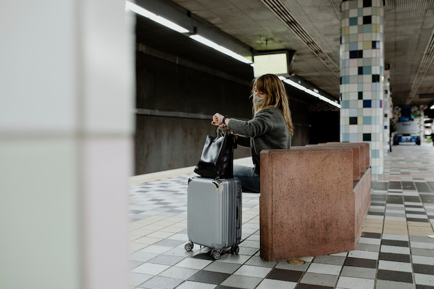 Vrouw kijkt op haar horloge terwijl ze op de trein wacht tijdens de pandemie van het coronavirus