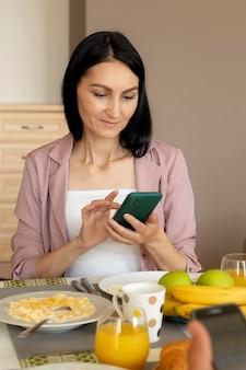 Vrouw kijkt op haar telefoon tijdens het wachten op het ontbijt