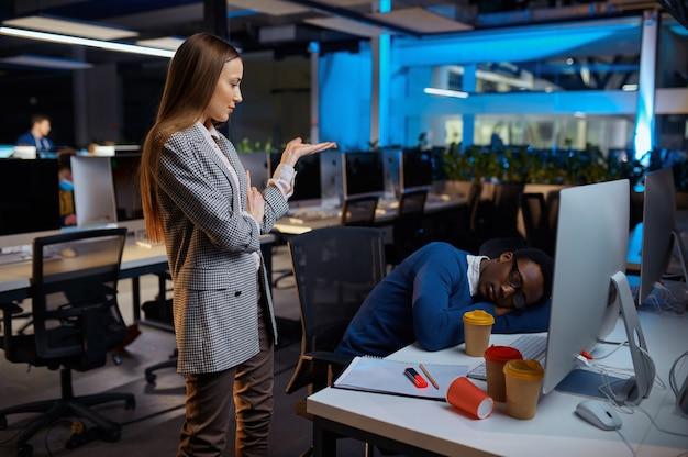 Vrouw kijkt op slapende manager, nachtkantoor levensstijl. vermoeide mannelijke personen op laptop, donker interieur, moderne werkplek