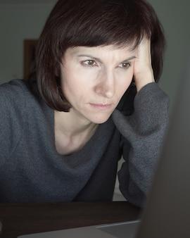 Vrouw kijkt 's avonds laat naar laptopscherm.