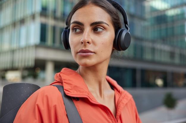 Vrouw kijkt terug keert terug van fitnesstraining luistert muziek via koptelefoon draagt rode anorak draagt opgerolde karemat poses tegen wazige stad