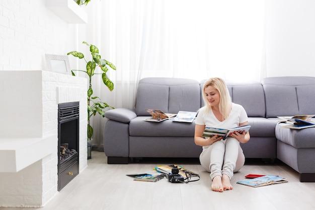 Vrouw kijkt thuis naar fotoboeken