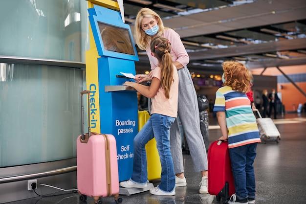 Vrouw kijkt trots naar een meisje bij een incheckautomaat