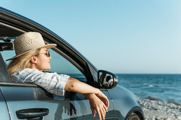 Vrouw kijkt uit autoraam op zoek naar zee