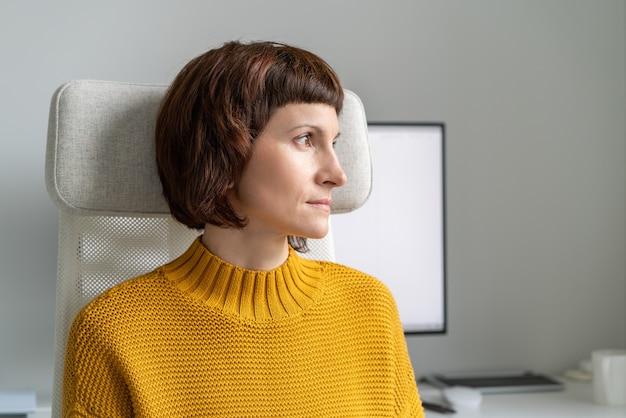 Vrouw kijkt uit het raam en neemt een pauze van het werk