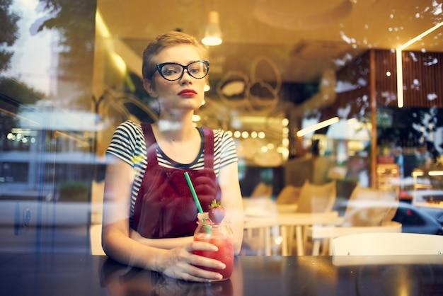 Vrouw kijkt uit het raam naar de straatcafé cocktaildrank levensstijl