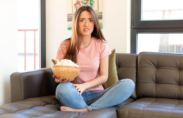 Vrouw kijkt verbaasd en verward, lipbijtend met een nerveus gebaar, het antwoord op het probleem niet wetend