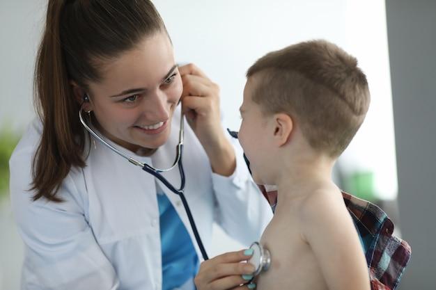 Vrouw kinderarts luistert naar de phonendoscope van het kind in de kliniek