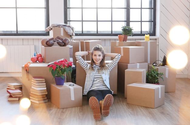 Vrouw klaar met lading pakketten en zit op de vloer