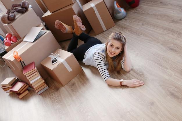 Vrouw klaar met vrachtpakketten en ligt op de grond en glimlacht