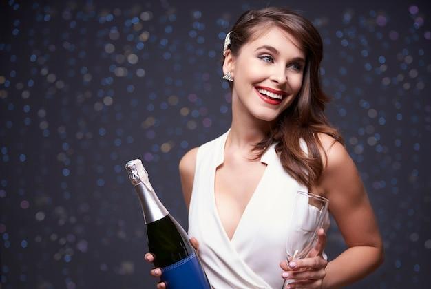 Vrouw klaar om champagne te gieten