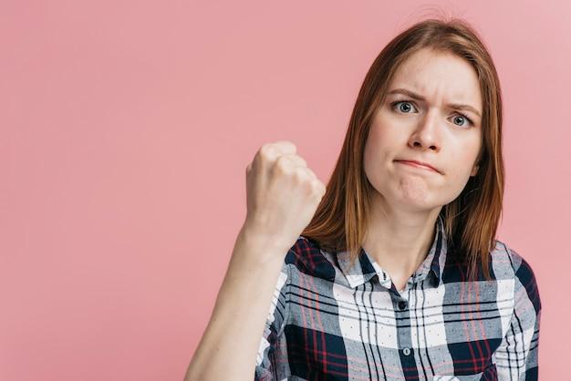 Vrouw klaar om met roze achtergrond te vechten
