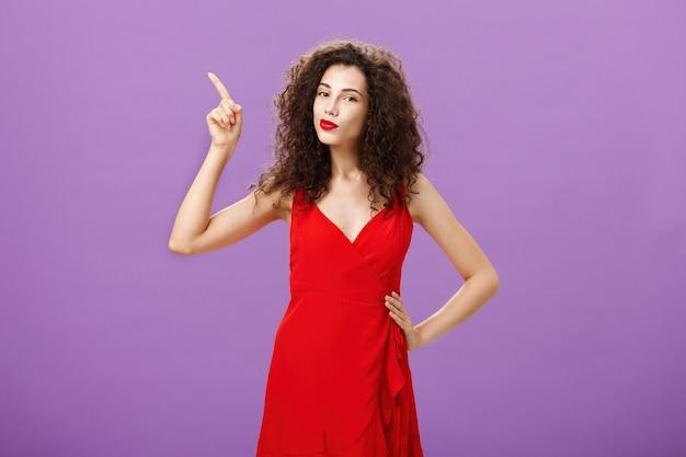 Vrouw klaar om te schitteren op de dansvloer in elegante rode jurk met sensuele make-up en krullend kapsel poi...