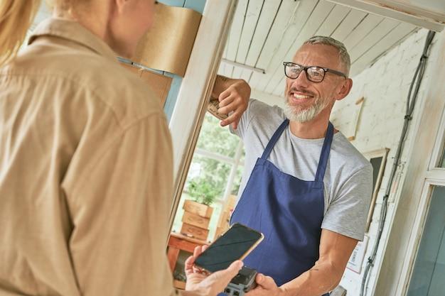 Vrouw klant betalen met behulp van smartphone aan blanke man