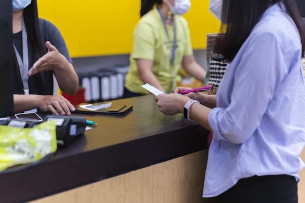 Vrouw klant met transactiebon met creditcard bij kassier balie