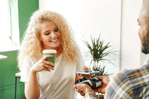 Vrouw klant van coffeeshop betalen voor koffie via mobiele telefoon met behulp van contactloze technologie close-up