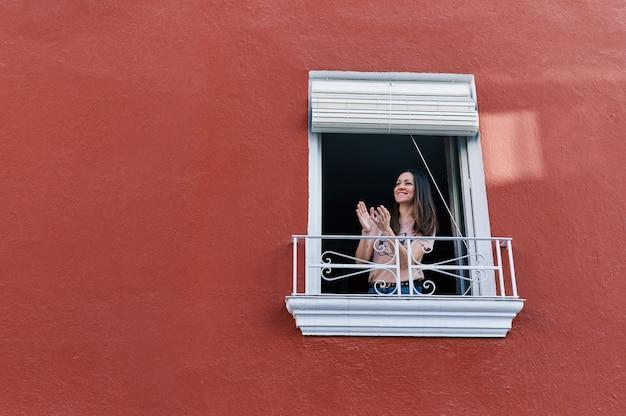 Vrouw klappen in het raam van haar huis met de rode gevel