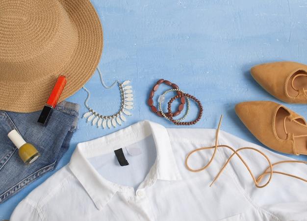Vrouw kleding, accessoires en make-up op lichte blauwe achtergrond