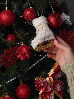 Vrouw kleedt de kerstboom aan met speelgoed