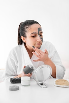 Vrouw klei gezichtsmasker thuis toe te passen
