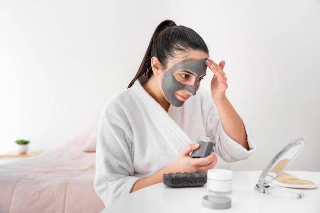 Vrouw klei gezichtsmasker zijaanzicht toe te passen