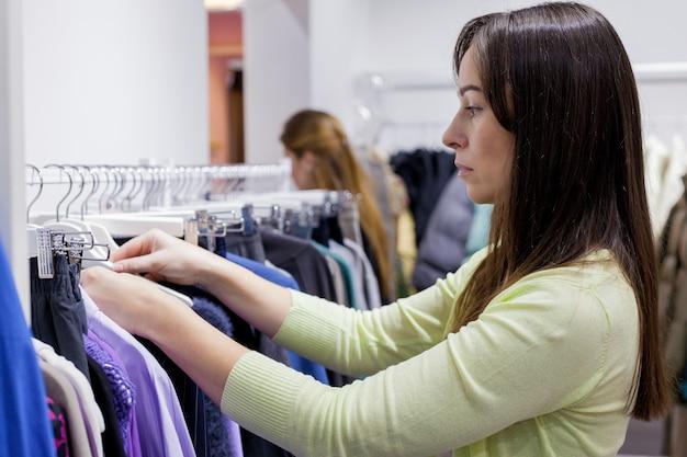 Vrouw kleren kiezen uit wit rek in mode kledingwinkel in winkelcentrum