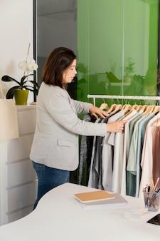 Vrouw kleren op rek schikken