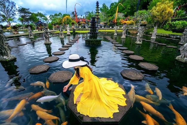 Vrouw kleurrijke vissen voederen in de vijver bij tirta gangga water palace in bali, indonesië