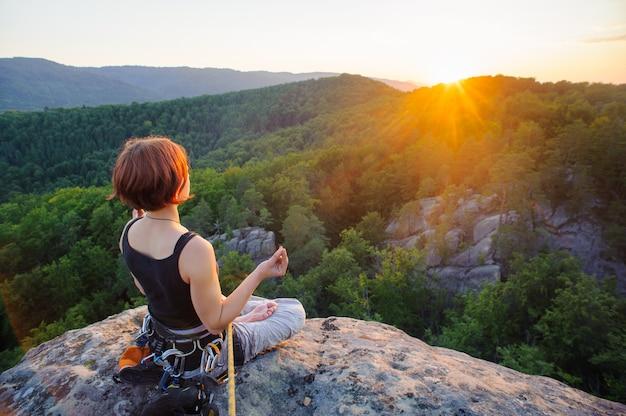 Vrouw klimmer zitten beveiligd met touw en mediteren