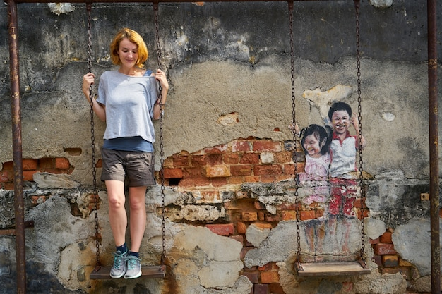 Vrouw klom naar een schommel met graffiti swing naast