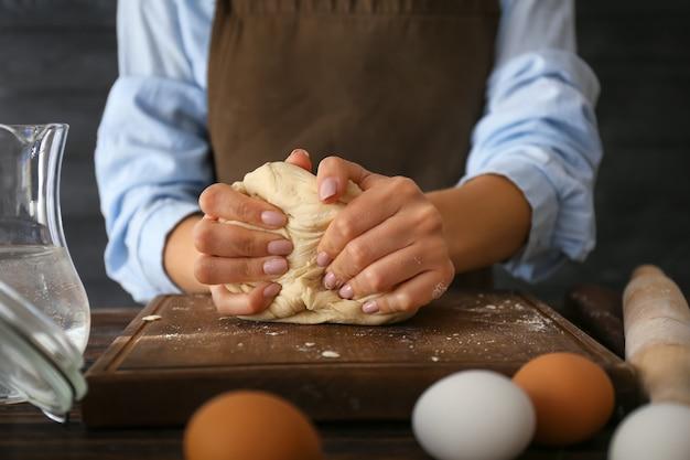 Vrouw kneed meel in de keuken, close-up