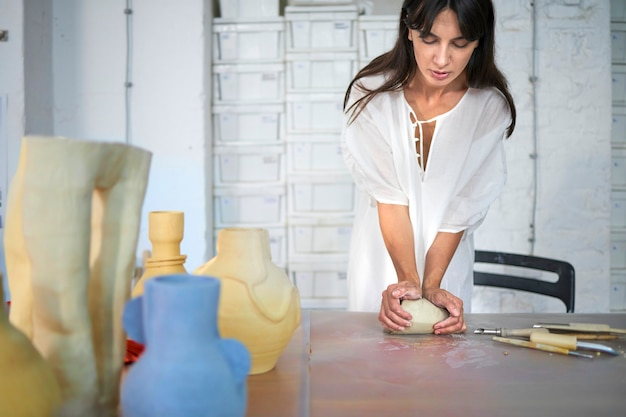 Vrouw kneedklei met haar handen in haar beeldhouwatelier
