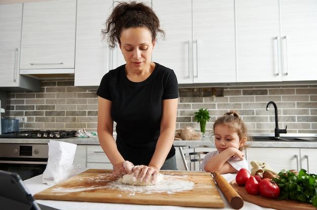 Vrouw kneedt deeg thuis in de keuken, naast dochter zittend op een stoel en kijkend naar het kookproces. familie tijd doorbrengen concept. kinderen leren koken.