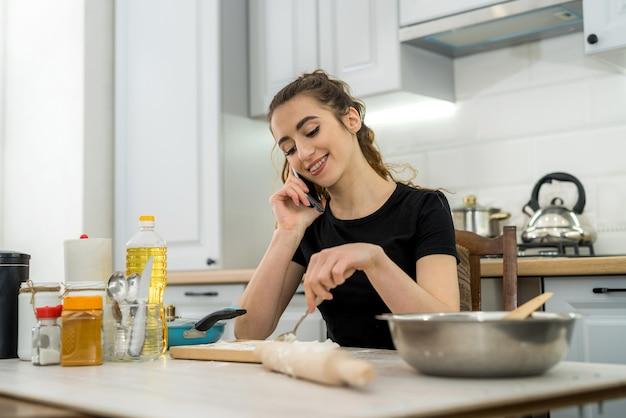 Vrouw kneedt het deeg met verschillende ingrediënten. gezond familievoedsel