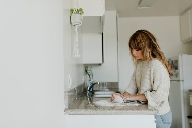 Vrouw kneedt zuurdesem in haar keuken tijdens quarantaine