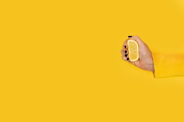 Vrouw knijpen een halve citroen op een gele achtergrond