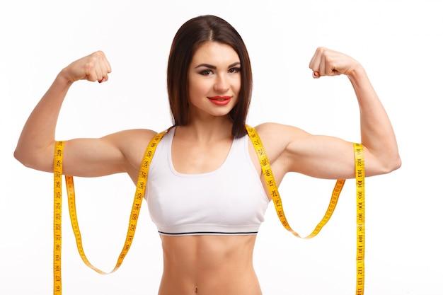 Vrouw knijpen zowel biceps en een meetlint