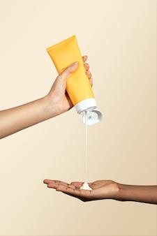 Vrouw knijpt crème uit een gele tube zonder label